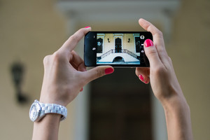 Pictures architectural sights on the mobile phone. Women's hands with red manicure holding a touchscreen phone closeup.
