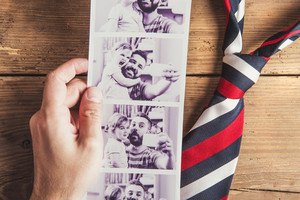 Pictures of father and daughter and colorful tie laid on wooden floor background.