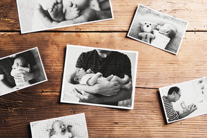 Pictures of young father and his cute newborn baby son laid on table. Fathers day concept. Studio shot on woden background.