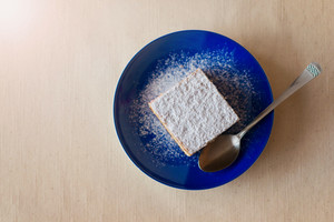 Piece of cake on a plate on white tablecloth background.