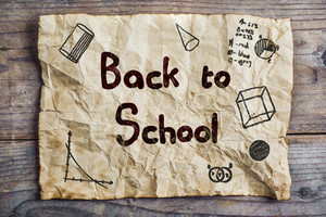 Piece of old rumpled paper with Back to school sign on wooden floor background