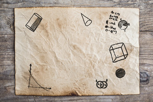 Piece of old rumpled paper with mathematics doodles on wooden floor background