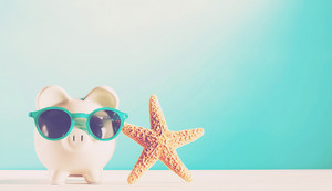 Piggy bank wearing a sunglasses with starfish on blue background