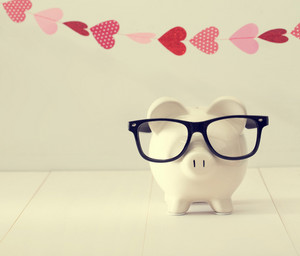 Piggy bank wearing black glasses with a garland of hearts