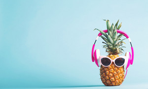 Pineapple with headphones and glasses on a bright background