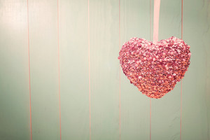 Pink shiny heart hanging on vintage green wood background