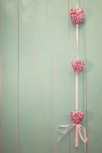 Pink shiny hearts hanging on vintage green wood background