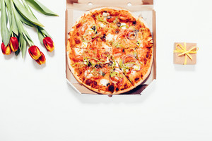 Pizza in a box, red tulips and a small box with a gift on a white background, top view