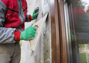 Plasterer spreading out plaster with trowel around the windows