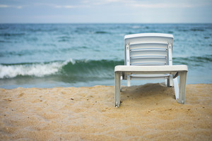 Plastic white lounge chair on empty beach.   The sunbed stands on the sand near the water.