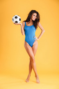 Playful pretty sporty smiling young woman in blue swimsuit posing holding ball isolated on the orange background
