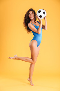 Playful pretty sporty smiling young woman in blue swimsuit posing on one leg isolated on the orange background