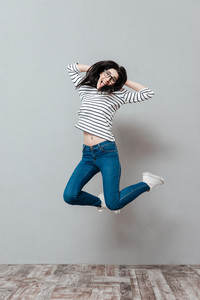 Playful young woman wearing eyeglasses jumping over grey background. Look at camera.