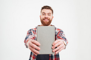 Porrait of a smiling happy bearded man showing book cover to camera over white background