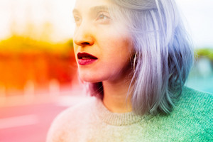 Portrait filtered colorful of young beautiful caucasian purple grey hair woman outdoor in the city overlooking pensive - thoughtful, serious, thinking future concept