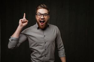 Portrait of a an excited happy bearded man in eyeglasses pointing finger up isolated on the black wooden background