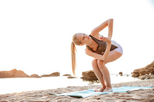 Portrait of a attractive young woman standing in yoga pose on beach