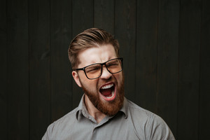 Portrait of a bearded casual man in eyeglasses screaming with eyes closed isolated on the black wooden background