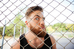 Portrait of a bearded funny man looking through the metal fence outdoors