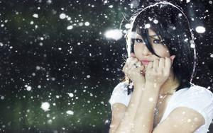 Portrait of a beautiful asian girl under snowfall