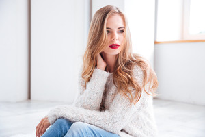 Portrait of a beautiful blonde girl wearing sweater and red lipstick while sitting on the floor at home