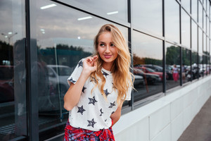 Portrait of a beautiful cheerful young woman standing outdoors at the glass building