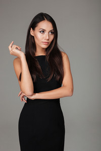 Portrait of a beautiful classy woman in black dress posing isolated on a gray background