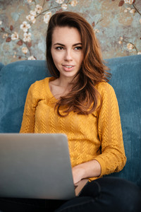 Portrait of a beautiful pensive woman sitting on the couch while using laptop and searching idea