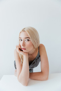 Portrait of a beautiful relaxed blonde girl looking at camera isolated on the grey background