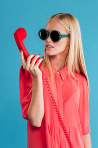 Portrait of a beautiful stylish blonde in sunglasses holding red telephone tube isolated on a blue background