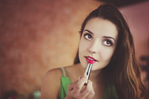 Portrait of a beautiful woman applying a lipstick on lips isolated on a white background