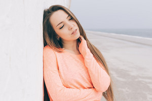 Portrait of a beautiful young brunette woman with long hair on the beach