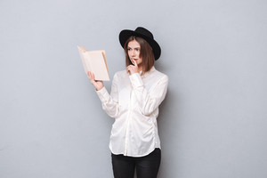 Portrait of a beautiful young concentrated woman in hat reading book isolated on the gray background
