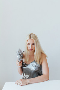 Portrait of a beautiful young fashion blonde girl holding water gun and sitting at the table isolated in the grey background