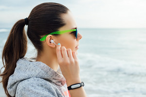 Portrait of a brunette in sportswear and sun glasses, she puts on the headphones and looks at the sea