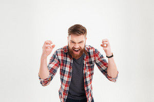 Portrait of a casual angry man screaming with raised arms isolated on a white background