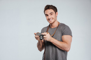 Portrait of a casual happy man with retro camera isolated on a white background