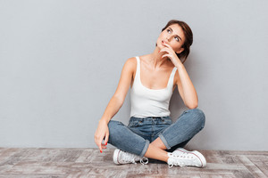 Portrait of a casual happy wondering woman sitting on the floor on gray background