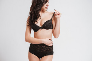 Portrait of a charming brunette woman in black lingerie posing and looking away isolated on a white background
