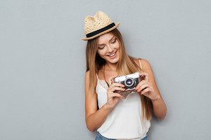 Portrait of a charming smiling woman in hat looking at retro camera isolated on a gray background