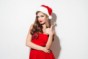 Portrait of a charming young woman in red christmas outfit pointing finger away isolated over white background