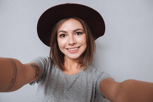Portrait of a charming young woman making selfie photo over gray background