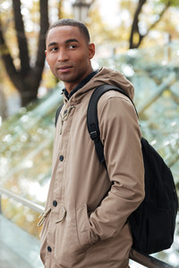 Portrait of a cheerful african young man walking on the street. Looking aside.