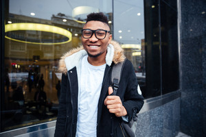 Portrait of a cheerful african young man walking on the street. Looking at camera.