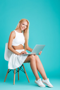 Portrait of a cheerful attractive woman using laptop computer and sitting on chair isolated on the blue background
