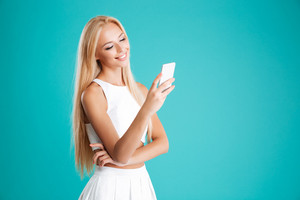Portrait of a cheerful blonde girl holding mobile phone isolated on the blue background