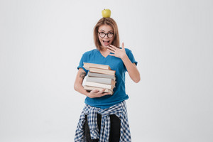 Portrait of a cheerful female student in eyeglasses with apple on her head holding stack of books isolated on the white background
