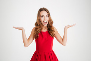 Portrait of a cheerful happy brunette woman in red santa claus dress holding copyspace on two palms over white background