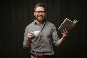 Portrait of a cheerful happy man in eyeglasses and shirt reading book and holding cup of coffee isolated on a black wooden background
