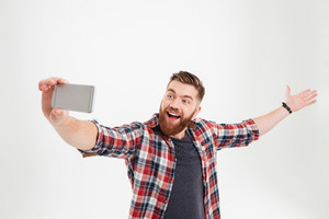 Portrait of a cheerful happy man taking selfie with raised hand over white background